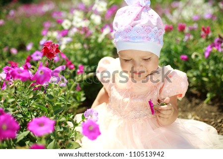 Little child girl enjoy flower in summer garden