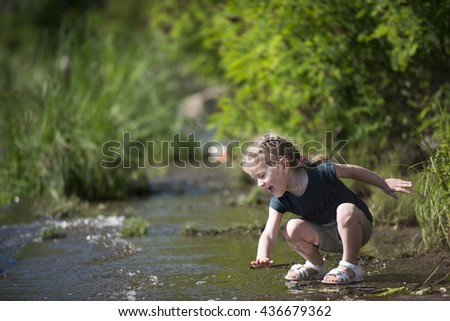 little child girl girl having fun outdoors near a water, on beach, in summer - stock photo