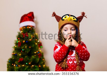 little child girl in front of a christmas tree making a wish - stock photo