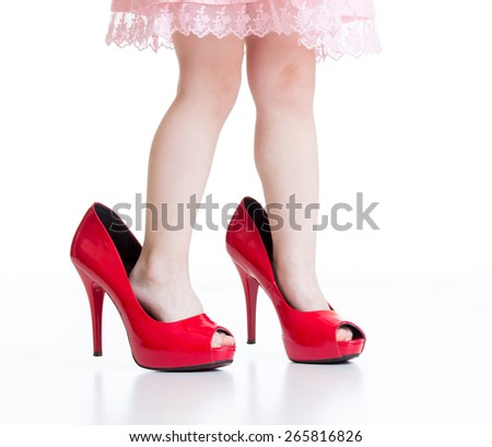 Little child girl playing with mommy red shoes - stock photo