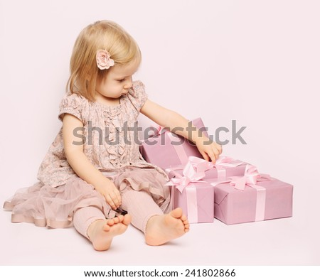 Little child girl with pink gift box birthday background - stock photo