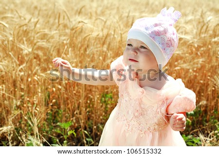Little child girl wondering in wheat field