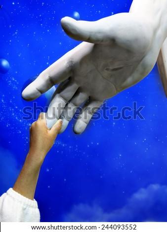 Little child holding hand of Jesus Statue showing faith spirit religion belief - stock photo