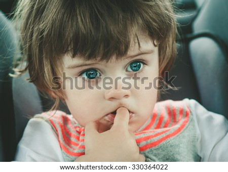 little child in car safety seat strapped