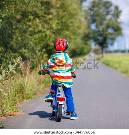 Little child in red safety helmet and colorful raincoat riding his first bike on summer day. Active leisure for kids outdoors. - stock photo