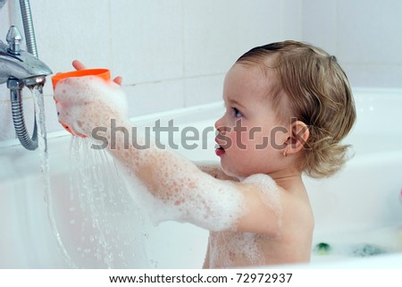 little child is playing with water in bath - stock photo