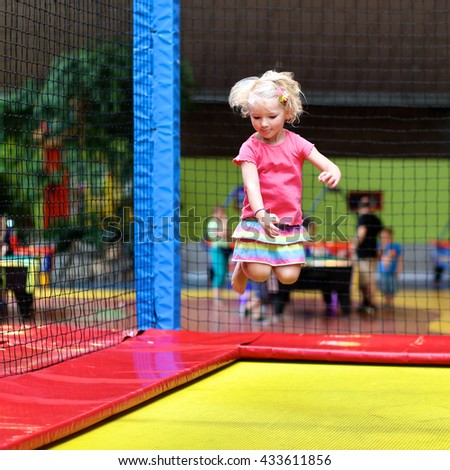 Little child jumping at trampoline in indoors playground. Active toddler girl having fun at sport center - stock photo