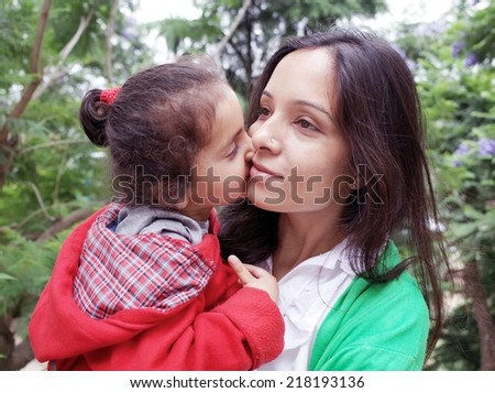 Little Child kissing her mother. - stock photo