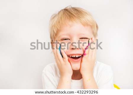 Little child laughing. Baby boy with hands in paint. Child painted with fingers. Portrait of adorable blond boy isolated at white background. Close up of smiling face and hands of small boy. - stock photo