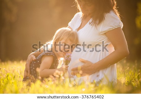 Little child listening baby in belly of her mother outdoor in sunny nature - stock photo