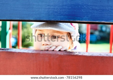 Little child looking through a crack between wooden planks - stock photo