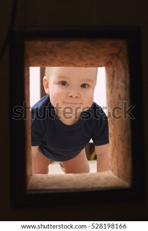Little child looks to hole in the wall
