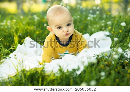 little child lying on a diaper the grass and smiling