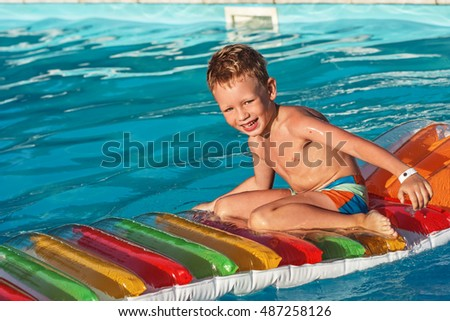 Little child on inflatable mattress in swim pool. Smiling boy playing and having fun in swimming pool with air mattress. Kid playing in water. Summer vacations concept. Boy swimming in pool water.