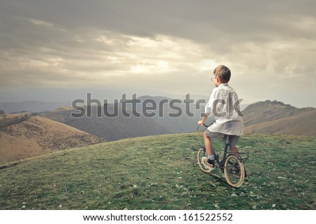 little child pedaling a bicycle in the mountain - stock photo