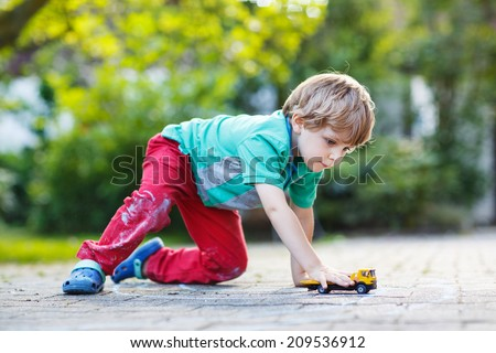 Little child playing with car toy in summer garden - stock photo