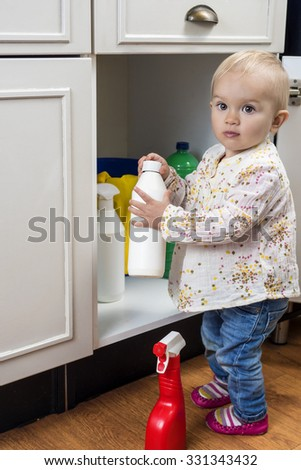 Little child playing with cleaning products at home - stock photo