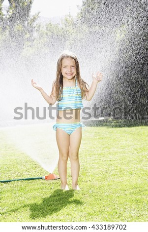 Little child playing with lawn sprinkler in a hot summer day - stock photo
