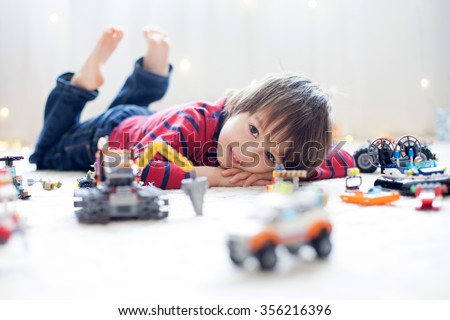 Little child playing with lots of colorful plastic toys indoor, building different cars and objects - stock photo