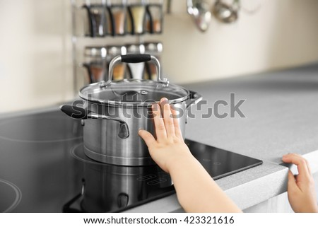 Little child playing with pan and electric stove in the kitchen - stock photo