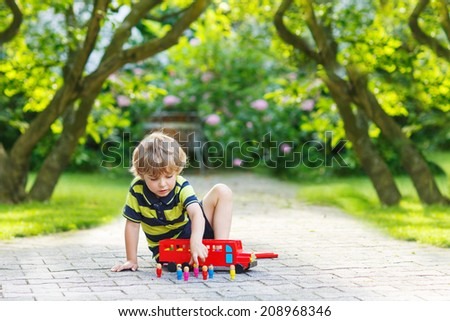 Little child playing with red bus and toys in summer garden - stock photo