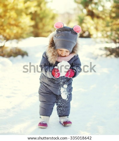 Little child playing with snowball in winter day - stock photo