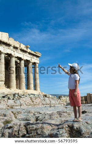 Little Child points to Facade of ancient temple Parthenon in Acropolis Athens Greece on the blue sky background - stock photo