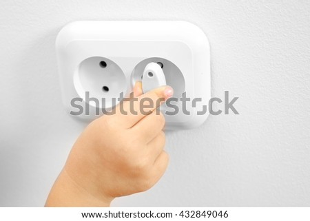 Little child putting plug in power socket