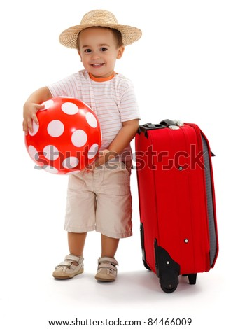 Little child ready for journey, holding big red dotted ball, wearing straw hat and standing near suitcase - stock photo