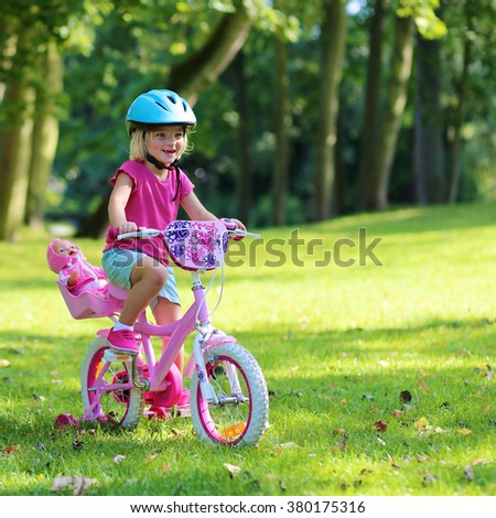 Little child riding her bicycle in the park. Cute preschooler girl learning to cycle with stabilisers wheels. Sportive kid enjoying sunny summer, spring or autumn day outdoors. - stock photo