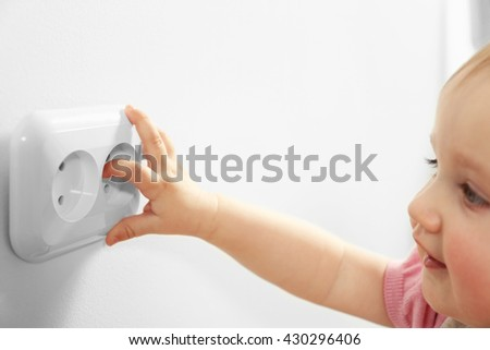 Little child's hand playing with power socket, closeup - stock photo