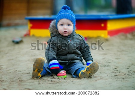 Little child, sitting  at the playground  - stock photo