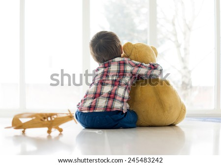 Little child sitting in living room with teddy bear - stock photo