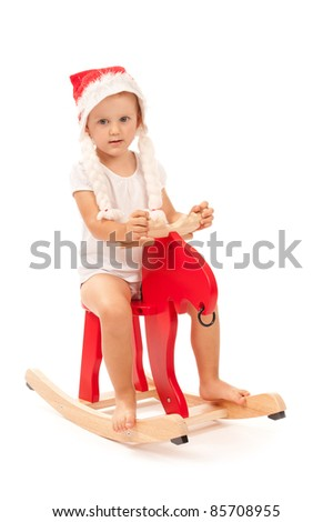 little child sitting on reindeer in studio on white background
