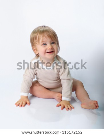 Little child sitting on the studio floor with smile