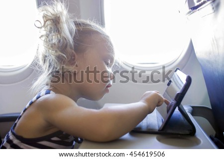 Little child using tablet in plane.