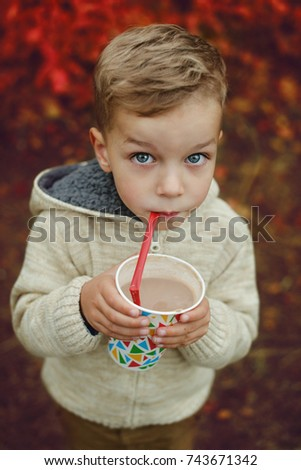 Little child walking in the forest and drinking hot cocoa at autumn day