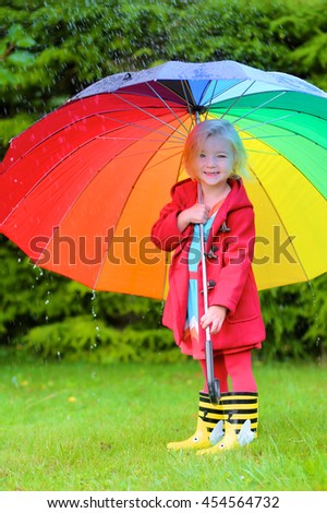 Little child with colorful umbrella playing in the garden during the rain. Cute toddler girl in red coat having fun outdoors by rainy fall weather. Preschooler kid in walking in the park.