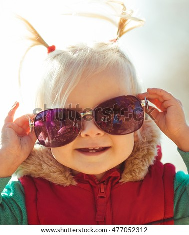 Little child with ponytails tries on large sunglasses
