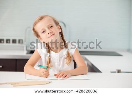 Little child writing. Preschool girl doing homework - stock photo