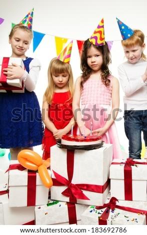 Little children celebrating birthday with cake - stock photo