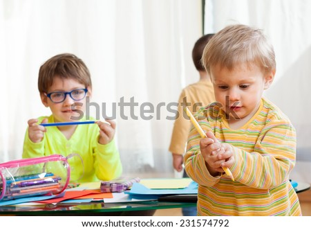 Little children drawing with crayons at  table. - stock photo