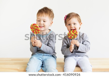 Little children eating lollipops. Happy kids with a big candy. Portrait of a happy little children - boy and girl. Beautiful kids against a white background - stock photo