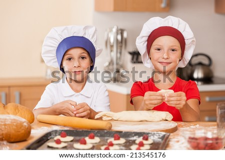 little children making cakes and smiling. two kids having fun at kitchen table  - stock photo