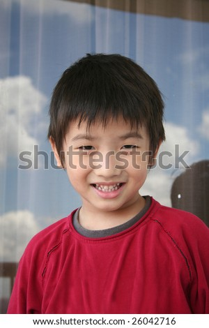 Little Chinese boy in red tee smiling happily
