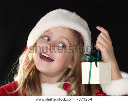 little Christmas girl dressed in Santa hat and dress while holding a gift