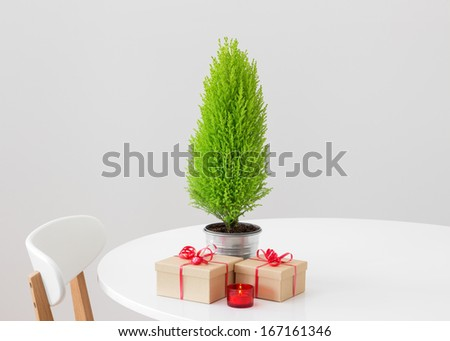 Little Christmas tree, gifts and candlelight on a white table. - stock photo