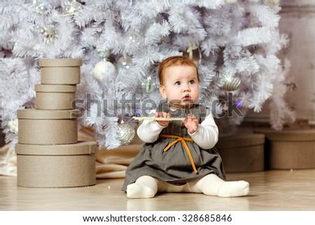 Little chubby baby girl in a gray dress sitting on the floor next to the gifts on the white background of Christmas tree in New year - stock photo