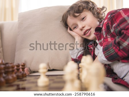 Little clever boy is smiling while playing chess. - stock photo