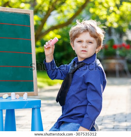 Little confused boy at blackboard practicing writing letters and mathematics, outdoor school or nursery. Kid learning and schoolboy concept. On summer sunny day. - stock photo